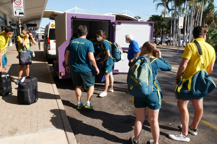 Olympic athletes unloading luggage from a vehicle outside Darwin Airport.