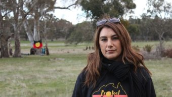 Lidia Thorpe, in an aboriginal flag shirt with the words 'protect country', stands in front of trees.