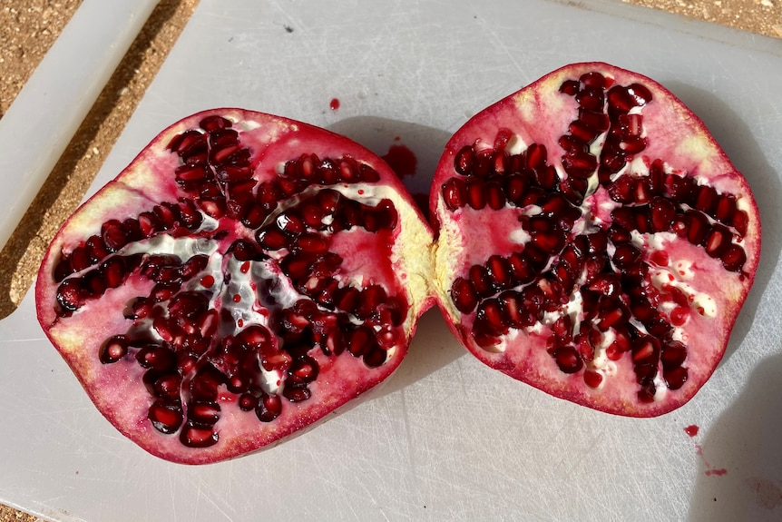 A red pomegranate, cut in half on a white chopping board.