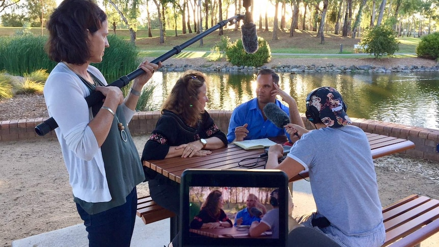 Producer holding microphones as Clarke and Smith talk while sitting at picnic table next to river