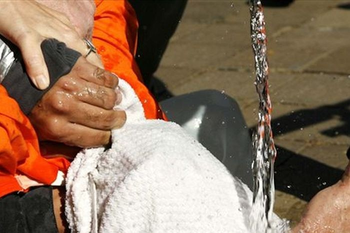 A demonstrator is held down during a simulation of waterboarding
