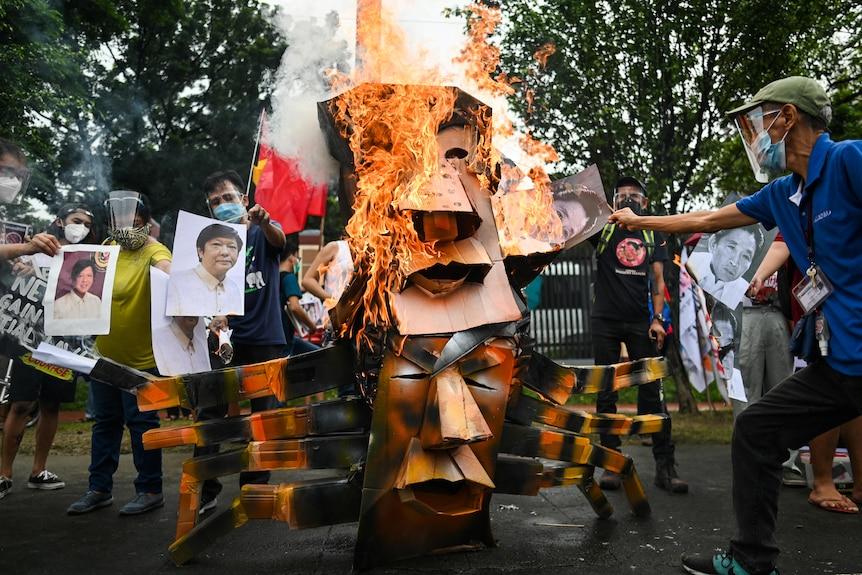 Un'effigie a due teste di Rodrigo Duterte e Ferdinand Marcos Jr. è stata data alle fiamme per le strade dai manifestanti con in mano delle foto.
