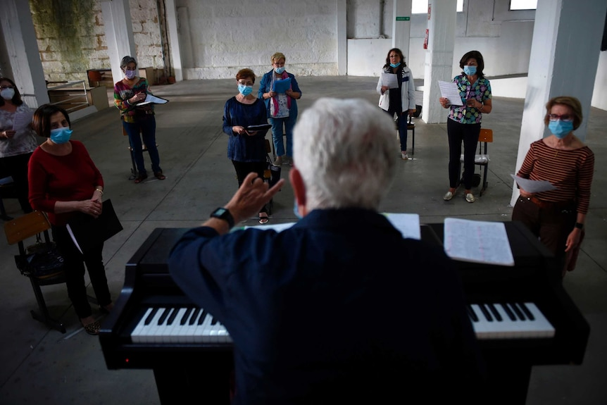 A choir director stands at a piano with a group of choristers spread out in front of him
