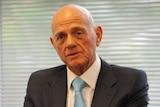 Head and shoulders shot of bald man in suit and tie