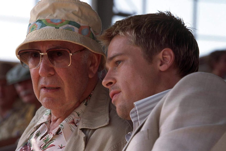 Carl Reiner wearing sunglasses and a hat sitting next to Brad Pitt
