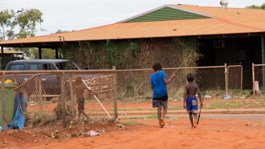 Two young indigenous boys walk barefoot, carrying spears.