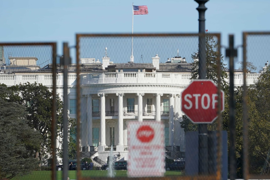 Security fencing surrounds the White House and a stop sign is pinned up in front of t
