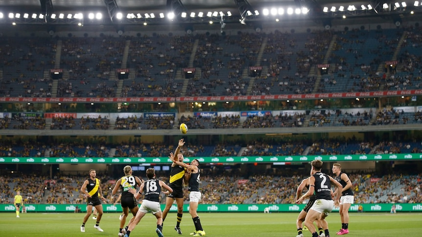 Richmond and Carlton players jostle for the ball in front of a crowd during a night match at the MCG.
