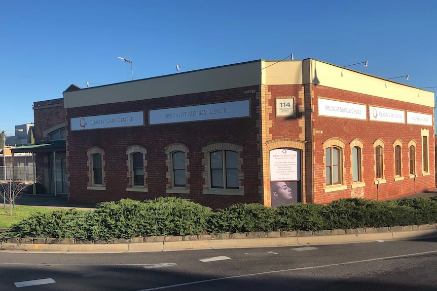 An older, red brick building on the corner of a road.