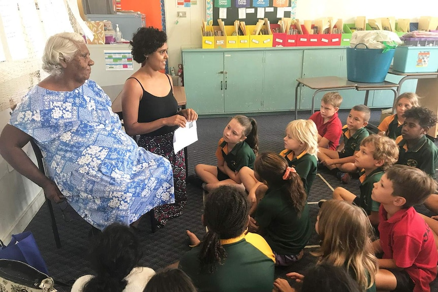 Students sit on floor of classroom at Mossman State School in far north Queensland, with teacher and Indigenous elder.