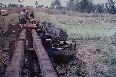 an old photo showing cane bins on top of a train underneath a small bridge