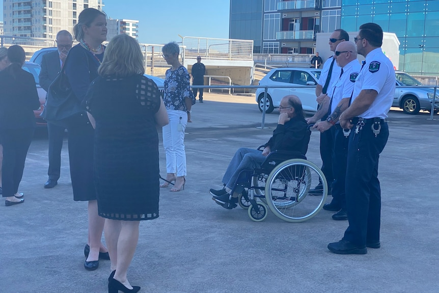 A man in a wheelchair with sheriffs officers and other people