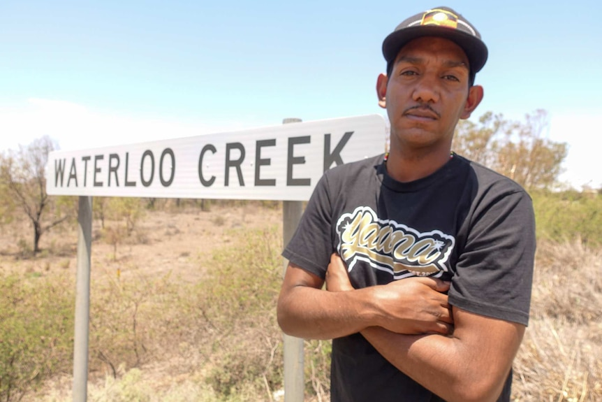 A man stands in front of the Waterloo Creek sign.