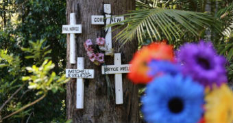 Four crosses are nailed to a three with coloured flowers in roadside tribute.