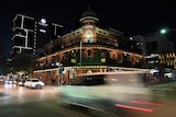 Cars pass through an intersection at night in an inner-city entertainment district