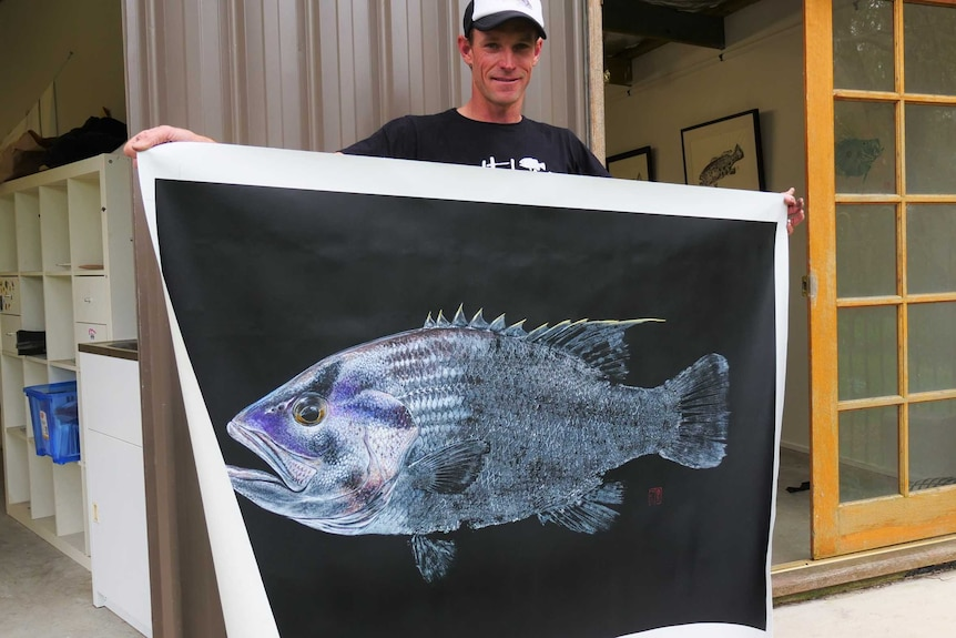 A man stands outside his studio holding a large canvas with a fish.