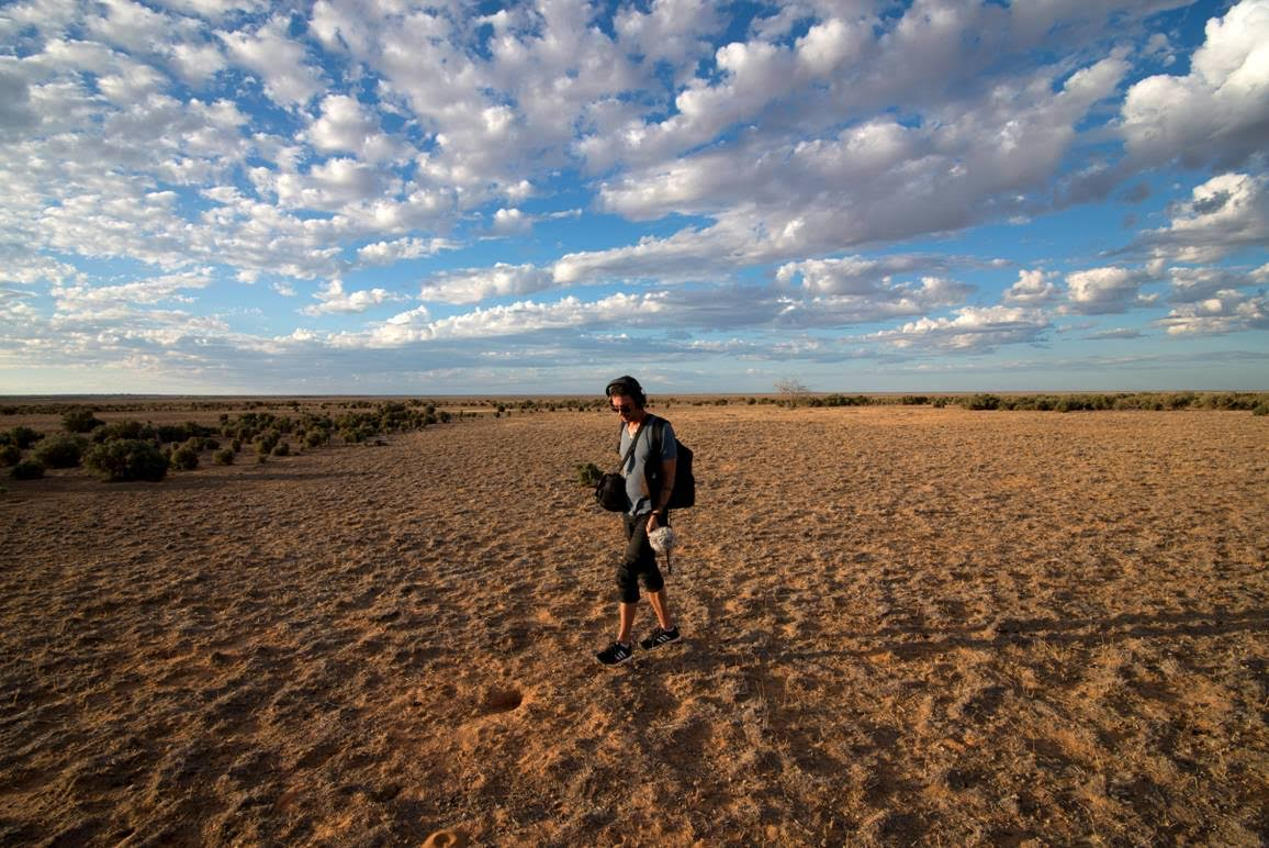 An Aboriginal man with audio recording equipment stands in a dessert, fluffy clouds in the sky