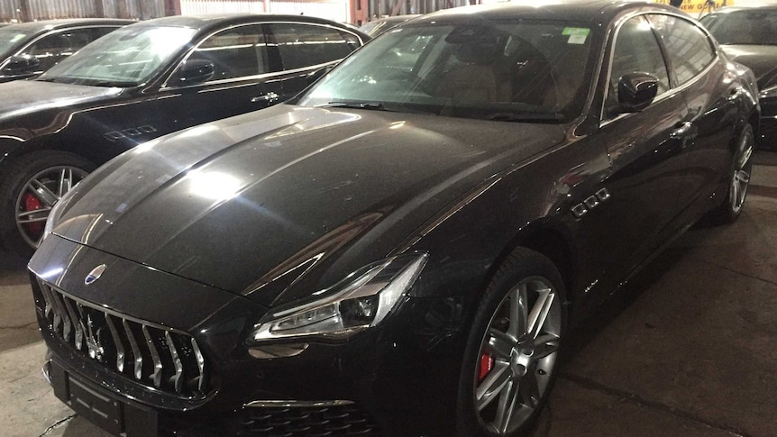 A row of black Maserati's sit in a shed.