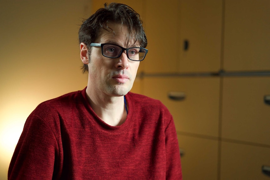 Australian journalist Scott McIntyre, wearing glasses and a red shirt, during an interview.