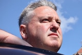 A close up shot of a man's head as he stares to the right of screen. He is leaning on at taxi and there is blue sky behind him.