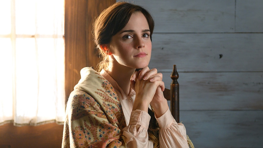 Emma Watson sitting at a desk in Little Women for list of films and TV shows dads and daughters should watch together