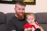 A medium shot of Nicholas wearing a dark grey t-shirt, holding his toddler son James, sitting on a couch, smiling at the camera.