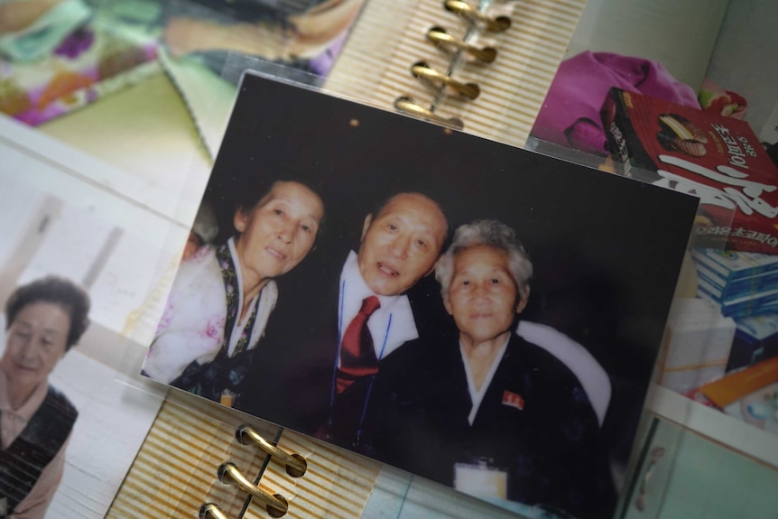 A photo shows a man sitting between two women and smiling.