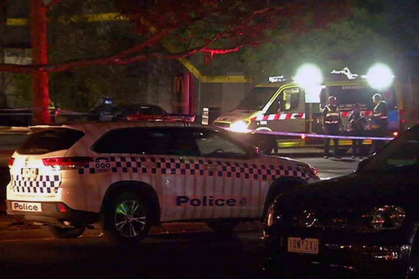 A police car and ambulance at the scene of the shooting at a fast food outlet carpark.