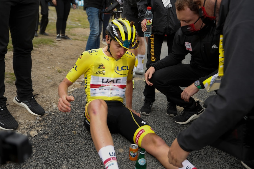 An exhausted cyclist wearing a yellow jersey sits on the ground looking at his leg while team officials check on him.