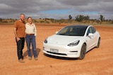 A man and a woman stand next to a white car with red desert dirt stretching behind them