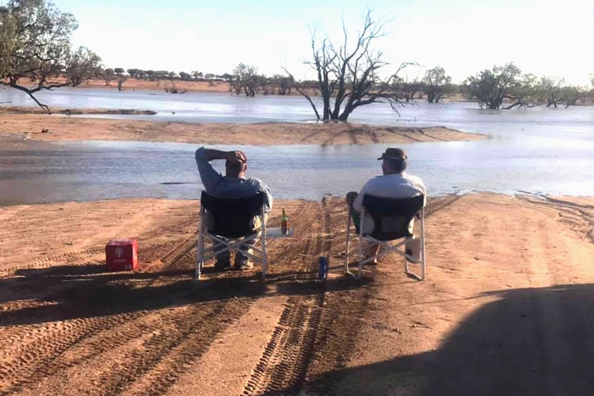 Two men sitting in camp chairs and staring at an expanse of flooded outback