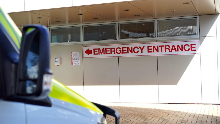 A sign on an outside wall reads Emergency Entrance with an arrow pointing left.