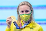 A blonde woman wearing a yellow face mask holds a gold medal