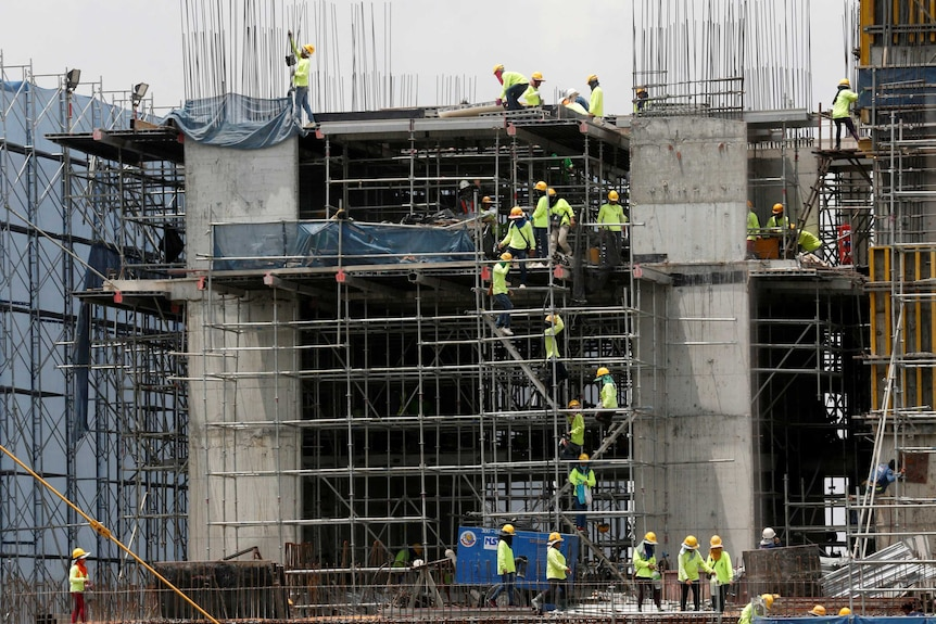 Labourers work at a construction site in downtown Bangkok. They are wearing high visibility clothing and helmets.