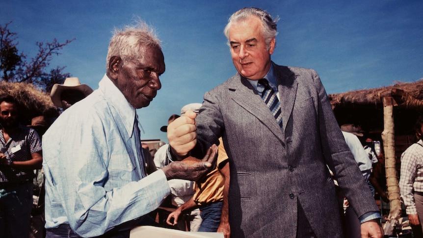 Gough Whitlam puts sand into Vincent Lingiari's hand.