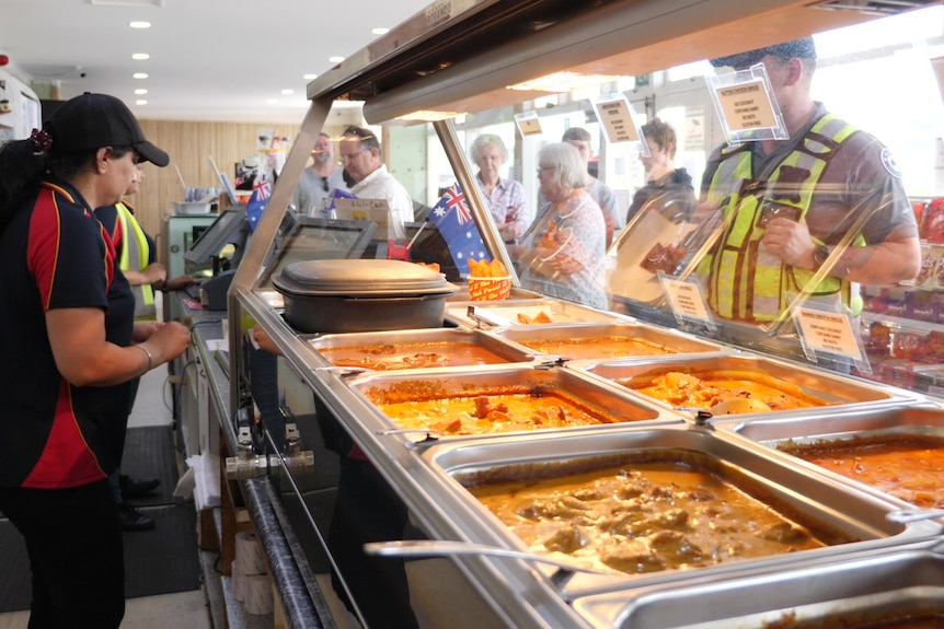 A line of hungry customers in front of a bain-marie.