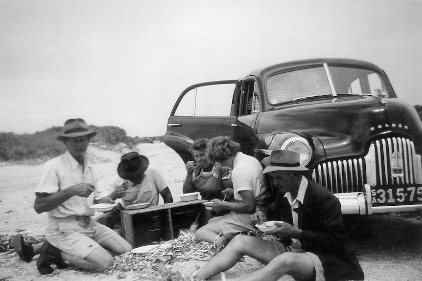 A family has a picnic next to its Holden