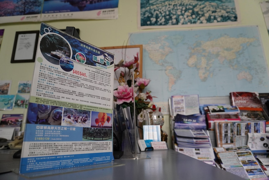A stack of travel posters and promotional materials in the office.