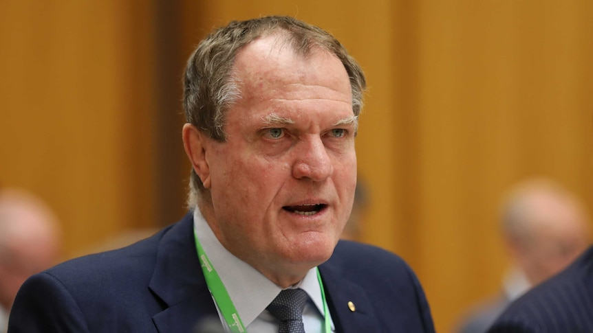 Chris Jordan stares intently while answering a question at Senate Estimates. His brow is furrowed.