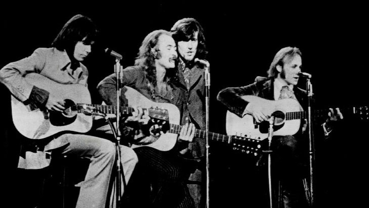 Black and white image of four musicians on stage.