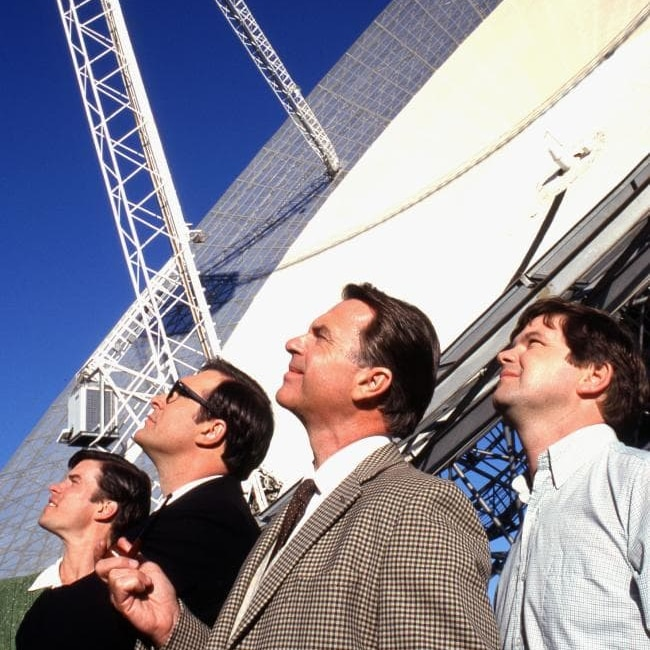 Sam Neill and two other cast members smile up at the Moon, sun on their faces.