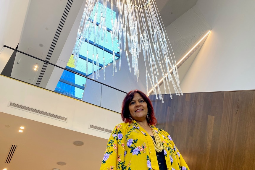 Women in a bright yellow floral jacket smiling underneath a dangling fibre-optic artwork