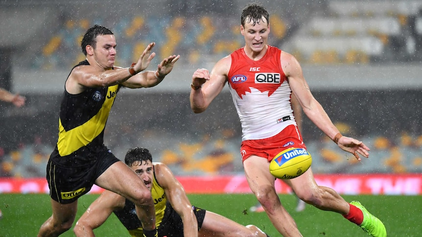 Jordan Dawson kicks a yellow ball past Daniel Rioli, who is approaching from Dawson's right with his arms raised