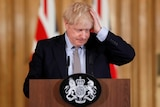Boris Johnson ruffling up his hair at a press conference