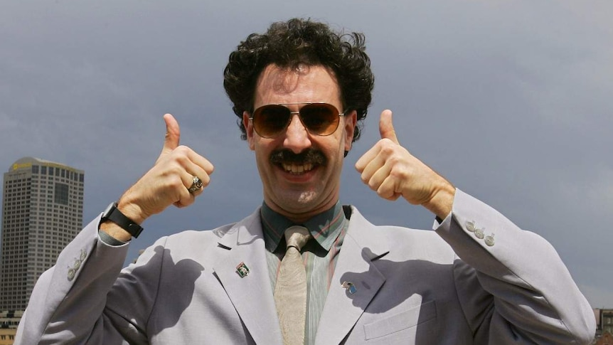 Borat in a suit and sunglasses gives a big smile and two thumbs up