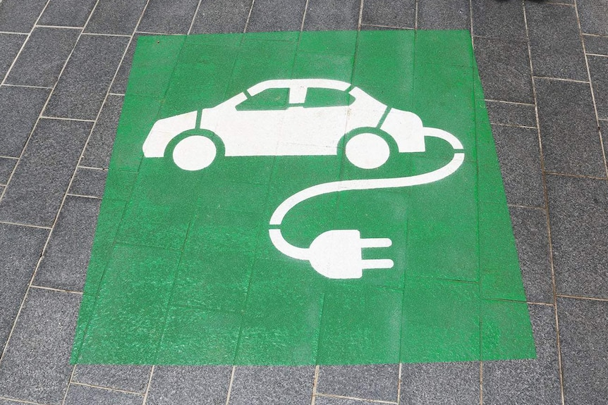 Green and white sign for charging station for an electric car parking space.