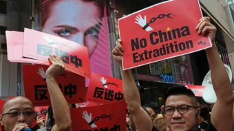 """Demonstrators hold up red signs saying """"no China extradition""""."""