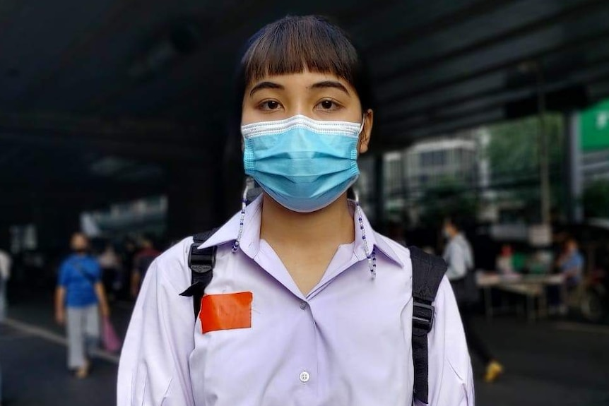 A young Thai woman in a face mask stands on a street