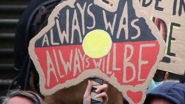 A protest sign reads 'Always Was Always Will Be', in front of police officers standing on Parliament's steps.