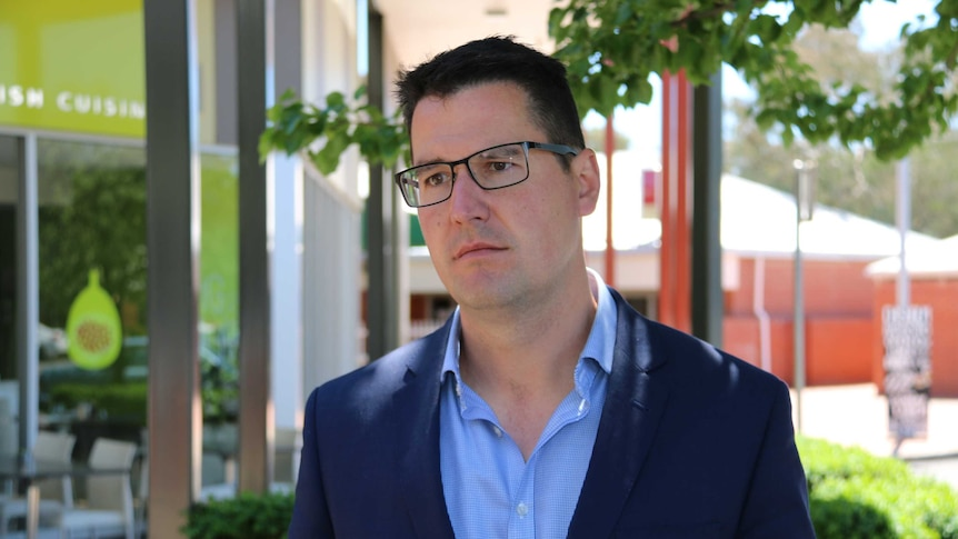 Zed Seselja stands in front of some shops and restaurants in Canberra.